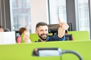 Portrait of happy mid adult businessman wearing headset while gesturing thumbs up in officeの写真素材 [FYI03657758]
