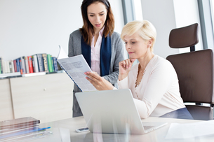 Businesswoman with female manager reading book at desk in officeの写真素材 [FYI03657759]
