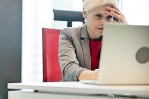 Tensed mature businesswoman using laptop at desk in officeの写真素材 [FYI03657798]
