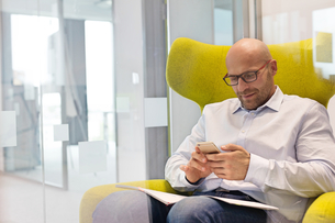 Mid adult businessman using mobile phone while sitting on chair at officeの写真素材 [FYI03657809]