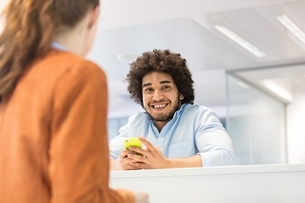 Smiling young businessman holding mobile phone with female colleague in foreground at officeの写真素材 [FYI03657810]