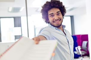 Portrait of smiling young businessman giving document in officeの写真素材 [FYI03657822]