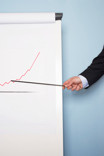 Businessman pointing at graph on flip chart against blue wallの写真素材 [FYI03657831]