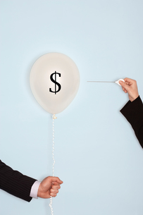 Cropped hands holding needle and popping balloon with Dollar Symbolの写真素材 [FYI03657833]