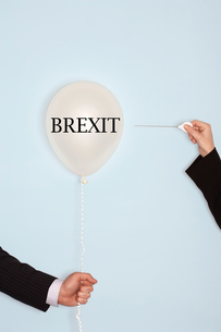 Cropped hands holding needle and popping balloon against light blue background with text saying Brexの写真素材 [FYI03657838]