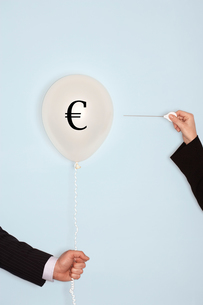 Cropped hands holding needle and popping balloon with EURO symbolの写真素材 [FYI03657839]