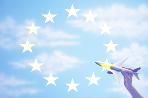 Person holding a toy plane flying in from of EU Flagの写真素材 [FYI03657909]