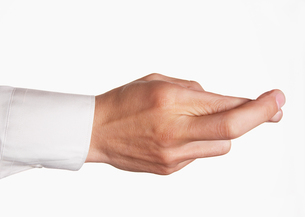 Closeup of hand with fingers crossed against white backgroundの写真素材 [FYI03657912]