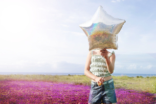 Front view of preadolescent girl holding star shaped balloon in front of her face while standing atの写真素材 [FYI03657919]