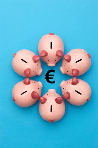 Piggy banks on blue background surrounding a Euro Symbolの写真素材 [FYI03657973]