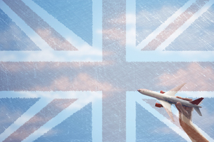 Toy plane flying in front of Union Jack flagの写真素材 [FYI03658009]