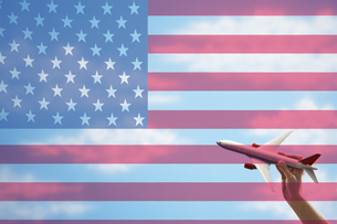 Toy plane flying in front of US flagの写真素材 [FYI03658017]