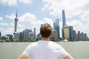 Rear view of man looking at Pudong skyline against cloudy skyの写真素材 [FYI03658060]