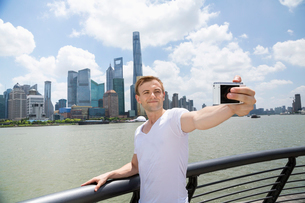 Mid adult man taking selfie while standing by railing against Pudong skylineの写真素材 [FYI03658062]