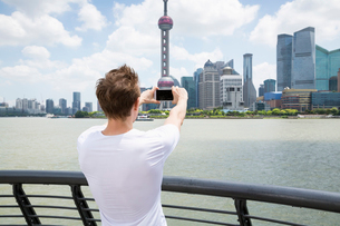 Rear view of man photographing Oriental Pearl Tower while standing by railingの写真素材 [FYI03658064]