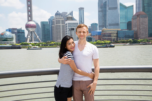 Portrait of smiling couple standing by railing with Shanghai skyline in backgroundの写真素材 [FYI03658065]