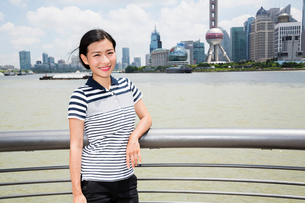 Portrait of woman leaning on railing by river with Oriental Pearl tower in backgroundの写真素材 [FYI03658068]