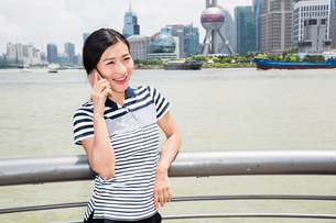 Happy young woman using smart phone while leaning on railing against Oriental Pearl Towerの写真素材 [FYI03658069]