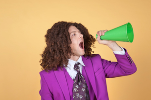 Caucasian man with afro wearing Purple Suit shouting from a coneの写真素材 [FYI03658091]