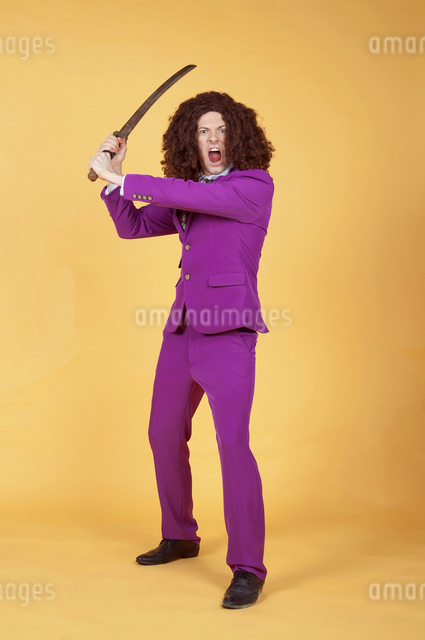 Caucasian man with afro wearing Purple Suit carrying swordの写真素材 [FYI03658110]