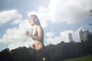 Fit and Healthy Chinese woman running in park at sun riseの写真素材 [FYI03658117]