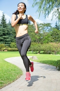 Fit and Healthy Chinese woman running in parkの写真素材 [FYI03658121]