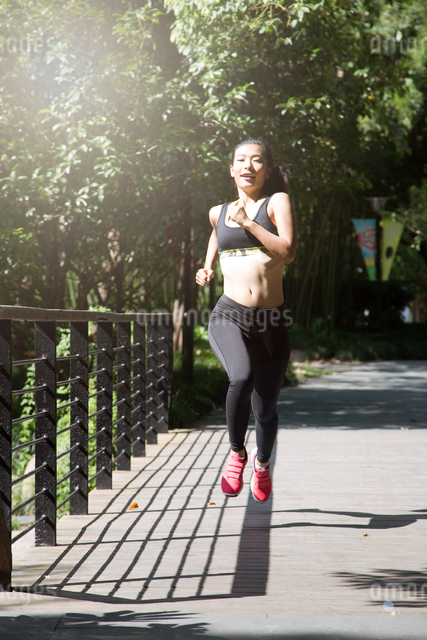 Fit and Healthy Chinese woman running in parkの写真素材 [FYI03658125]