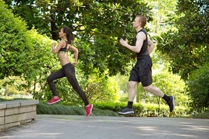 Side view of Multi ethnic couple running in parkの写真素材 [FYI03658136]