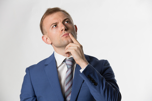 Businessman with finger on face thinkingの写真素材 [FYI03658149]