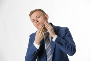 Businessman touching his face highlighting skin careの写真素材 [FYI03658162]