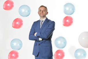 Businessman standing by falling  balloonsの写真素材 [FYI03658164]