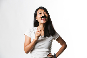 Chinese woman having fun with a fake mustacheの写真素材 [FYI03658165]