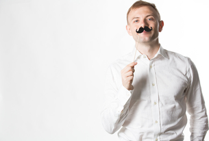 Portrait of an attractive young man wearing a retro style fake mustache.の写真素材 [FYI03658168]
