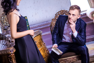 Loving mid adult man in suit looking at woman while sitting on chairの写真素材 [FYI03658169]