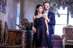 Thoughtful elegant couple looking away while standing by furniture at homeの写真素材 [FYI03658172]