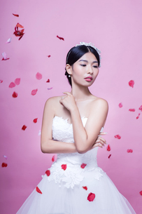 Beautiful bride with rose petals in mid-air standing against pink backgroundの写真素材 [FYI03658174]