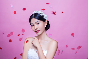 Portrait of beautiful bride with rose petals in mid-air against pink backgroundの写真素材 [FYI03658175]
