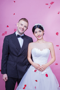 Portrait of happy wedding couple standing against pink backgroundの写真素材 [FYI03658176]