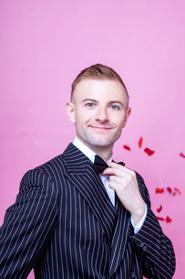 Portrait of smiling bridegroom in striped suit standing against pink backgroundの写真素材 [FYI03658180]