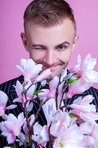 Portrait of bridegroom with artificial flowers winking against pink backgroundの写真素材 [FYI03658182]