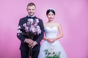 Portrait of multi-ethnic wedding couple holding flowers while standing against pink backgroundの写真素材 [FYI03658183]