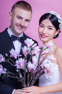Portrait of smiling wedding couple holding artificial flowers against pink backgroundの写真素材 [FYI03658184]