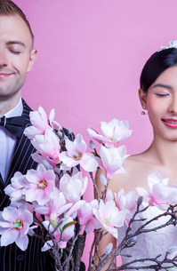 Smiling wedding couple with artificial flowers standing with eyes closed against pink backgroundの写真素材 [FYI03658185]