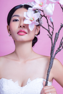Portrait of confident bride holding artificial flowers against pink backgroundの写真素材 [FYI03658186]