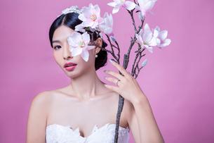 Portrait of confident bride holding artificial flowers against pink backgroundの写真素材 [FYI03658187]
