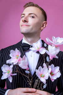 Portrait of confident bridegroom holding artificial flowers while standing against pink backgroundの写真素材 [FYI03658190]