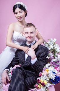 Portrait of confident wedding couple sitting against pink backgroundの写真素材 [FYI03658192]