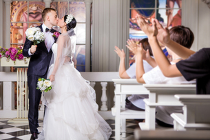 Wedding guests applauding while newlywed couple kissing in churchの写真素材 [FYI03658195]