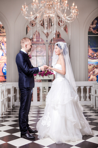 Full length side view of wedding couple exchanging rings in churchの写真素材 [FYI03658198]