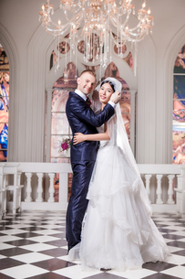 Side view portrait of smiling wedding couple standing in churchの写真素材 [FYI03658199]